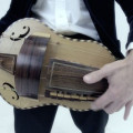 Hurdy Gurdy, flat back with guitar-shaped body made by Richard Smith, in black coffin-shaped case